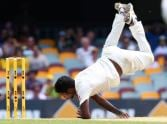 Varun Aaron falls over while bowling to Warner.
