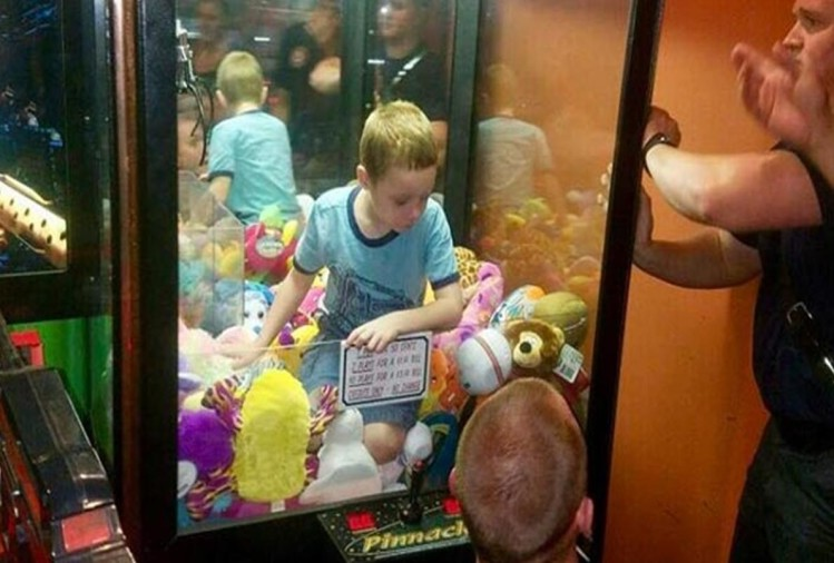 boy climbs into toy claw machine and strucked into it firefighter save him