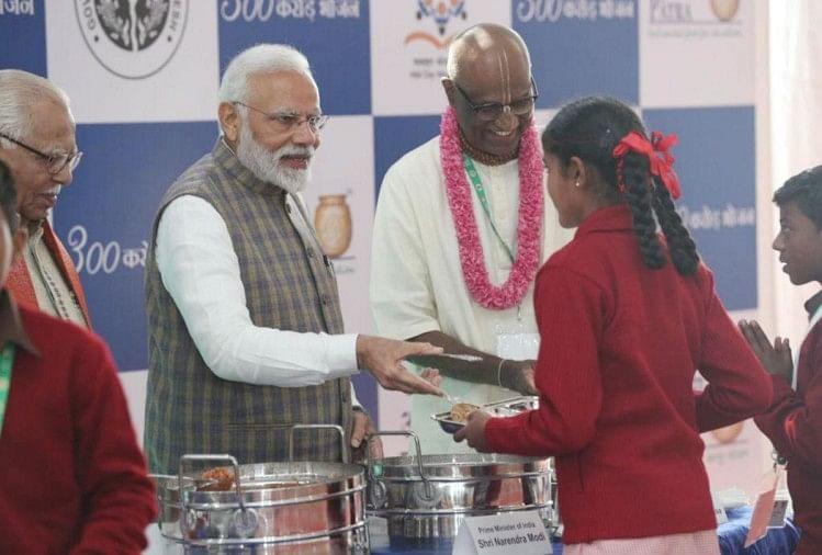स्कूली बच्चों को खाना परोसते प्रधानमंत्री मोदी