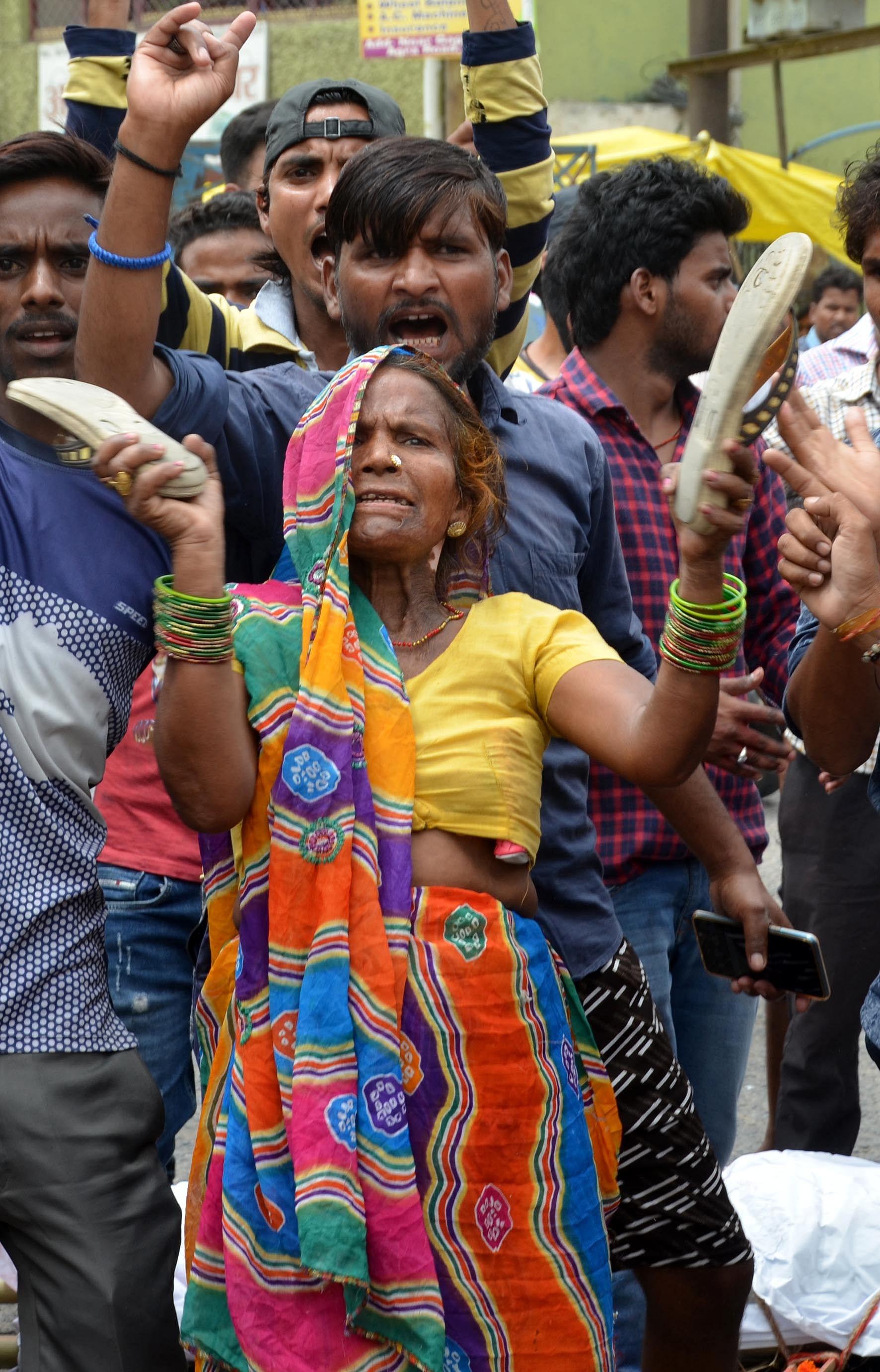 हाथरस अड्डा पर शव रखकर हाथों में चप्पल लेकर हंगामा करती महिला।