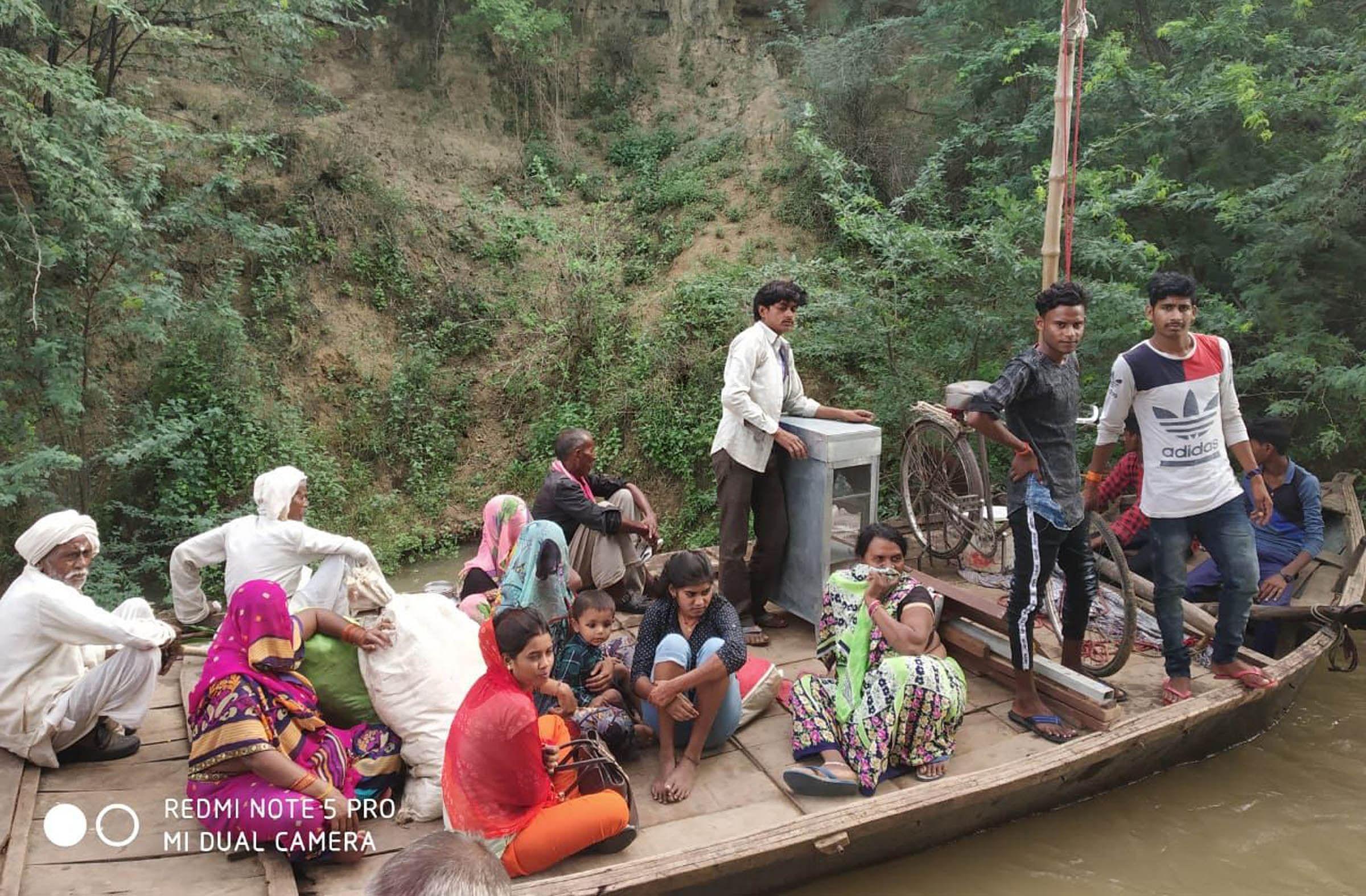 नाव से सुरक्षित स्थानों पर जाते बाढ़ प्रभावित।