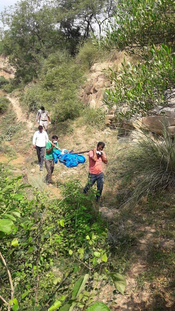 फोटो 1- जंगल से शव को बाहर निकालते ग्रामीण, कार्यवाही को अंजाम देते पुलिस के कर्मचारी, शव की जगह को म