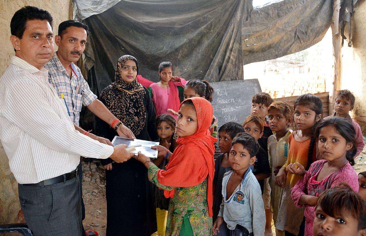 गहरा बाग की मलिन बस्ती में बच्चों पाठ्य सामग्री देते शिक्षा विभाग के कर्मचारी।