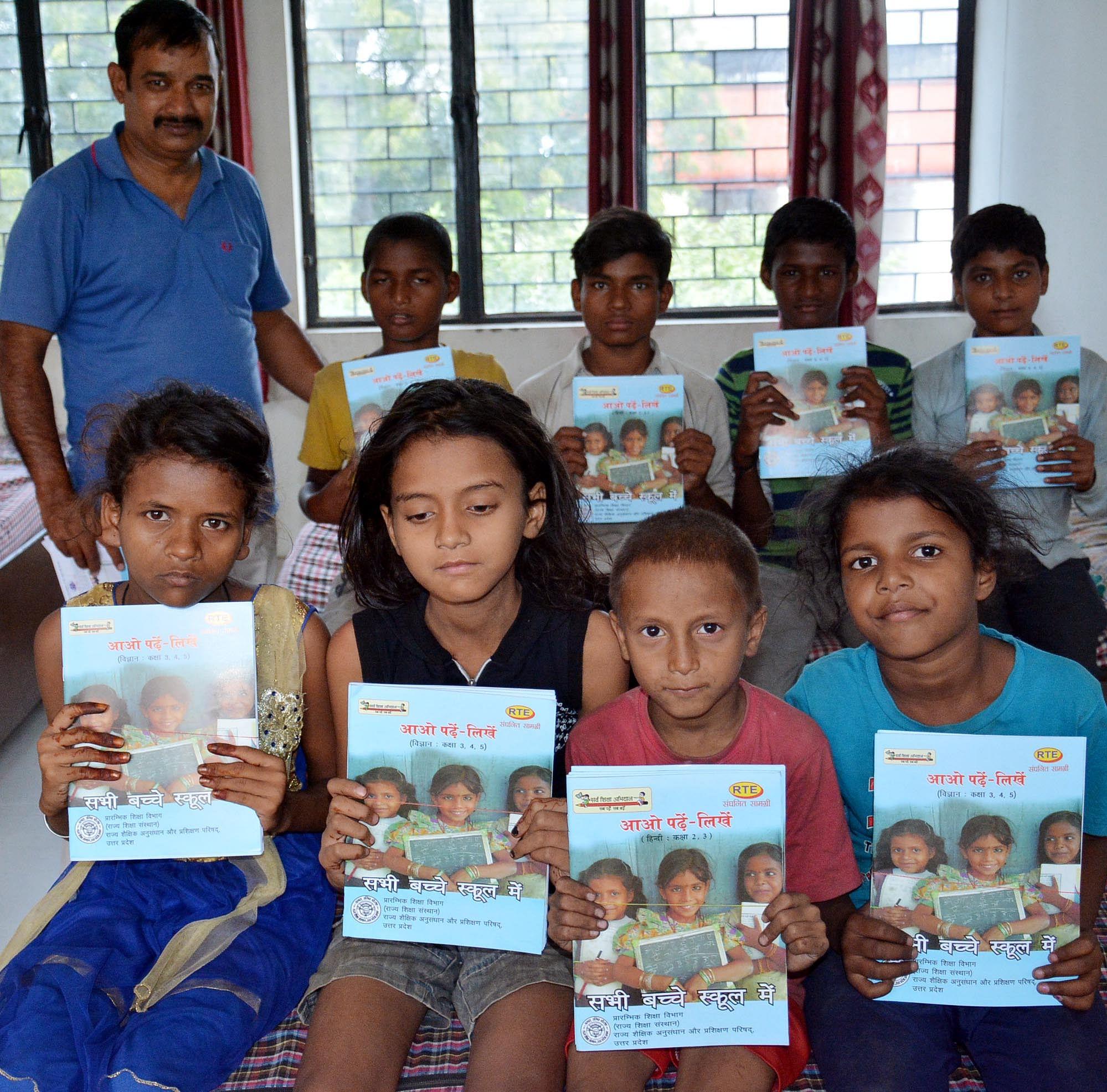 रेलवे रोड पर शाल्टर होम में  मलिन बस्ती के बच्चों को पुस्तक देते शिक्षा विभाग के कर्मचारी।