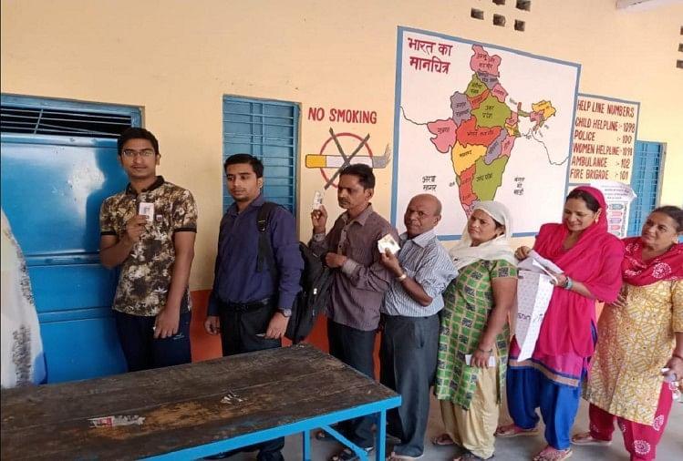 वोट डालने के लिए लाइन में लगे मतदाता