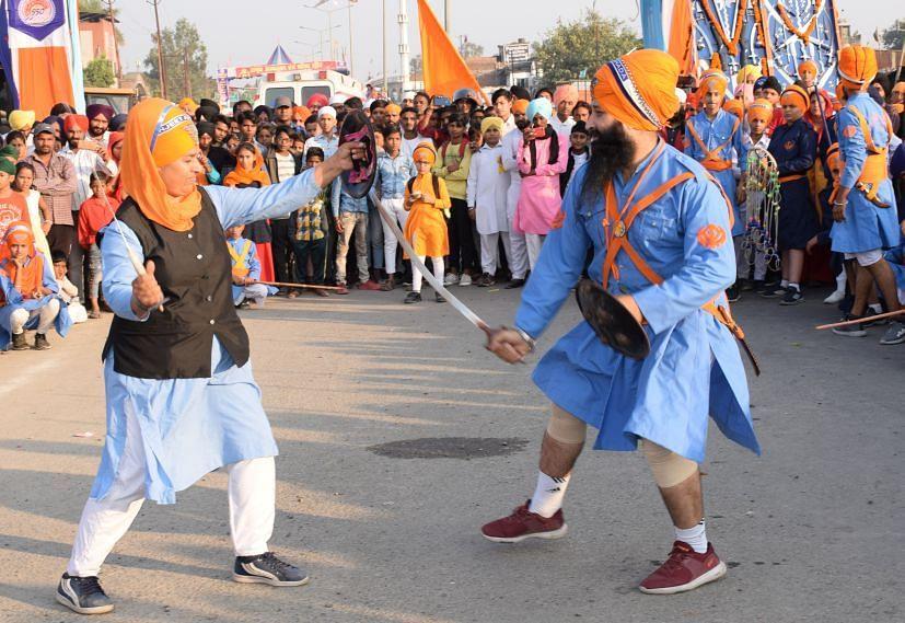 रुद्रपुर में निकले नगर र्कीतन में करतब दिखाती गतका पार्टी।