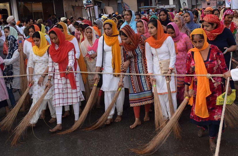 रुद्रपुर में निकले नगर कीर्तन में मुख्य पालकी के आगे सड़क की सफाई करती महिला श्रद्धालु।