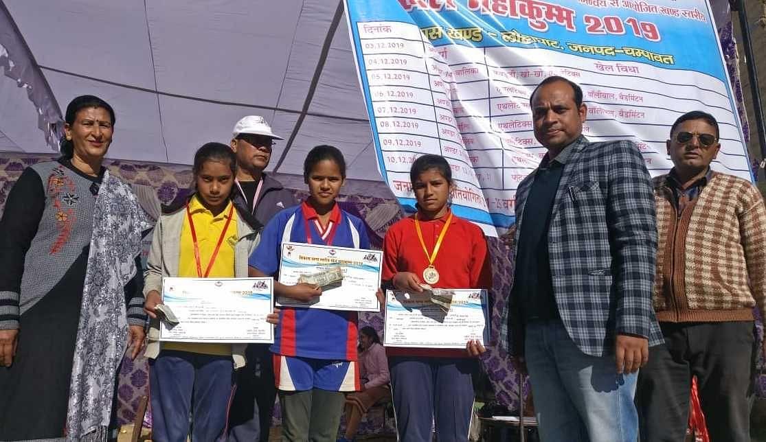 लोहाघाट खेल महाकुंभ में विजेता प्रियंका, भावना, रिया को पुरस्कृत करते बीईओ हरेंद्र साह।