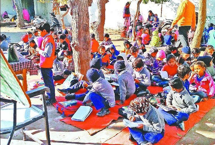 नीचे बैठकर पढ़ाई करते स्कूली बच्चे