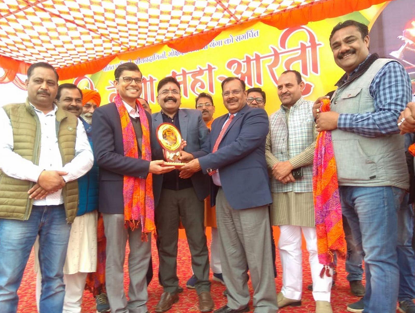 गंगा आरती का एक वर्ष पूरा होने पर शामिल हुए तत्कालीन डीएम दिनेश कुमार सिंह को सम्मानित किया गया।