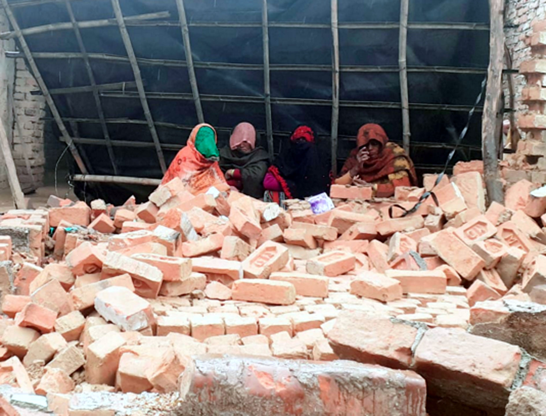 कासगंज के ढोलना में अतिक्रमण हटाने के दौरान ध्वस्त किए गए मकान के मलबे के पीछे बैठी महिलाएं प्रशा