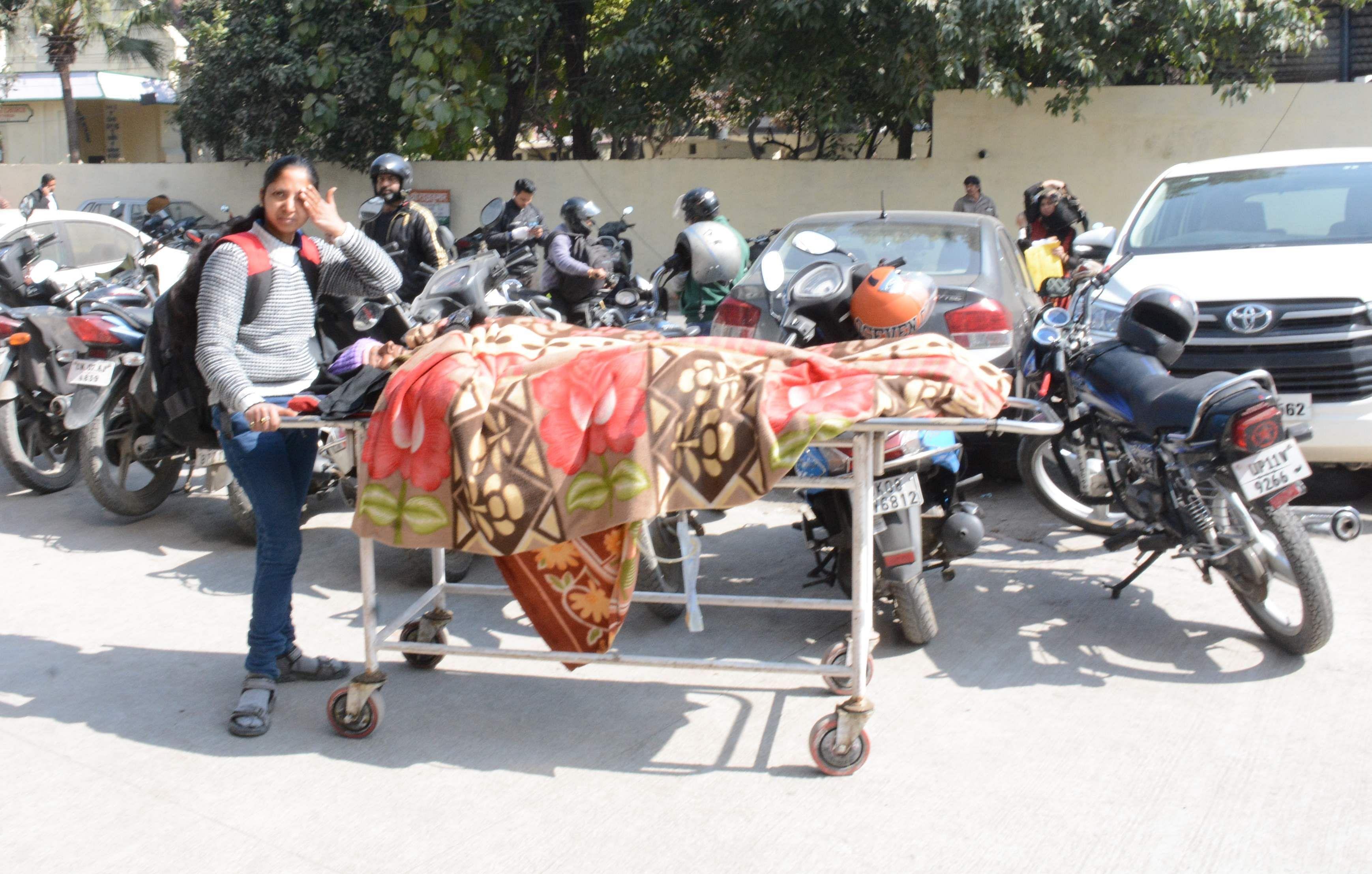 राजकीय दून मेडिकल चिकित्सालय के बाहर स्ट्रेचर में अपने परिजन को लिटाकर खड़ी युवती ।