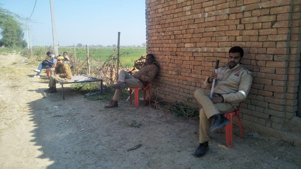 बिलायां में आरोपियों के घर के बाहर बैठी पुलिस।