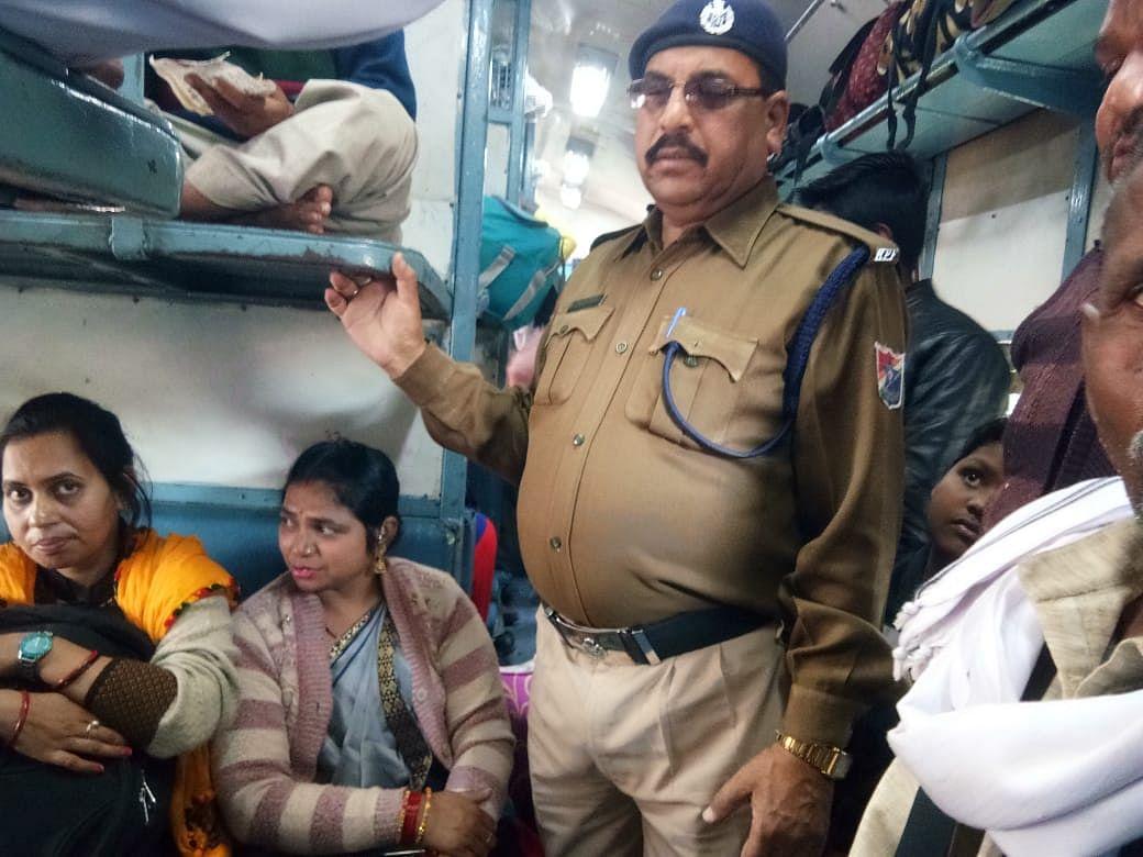 महिला कोच में बैठे यात्रियों को उतारते आरपीएफ कर्मी।