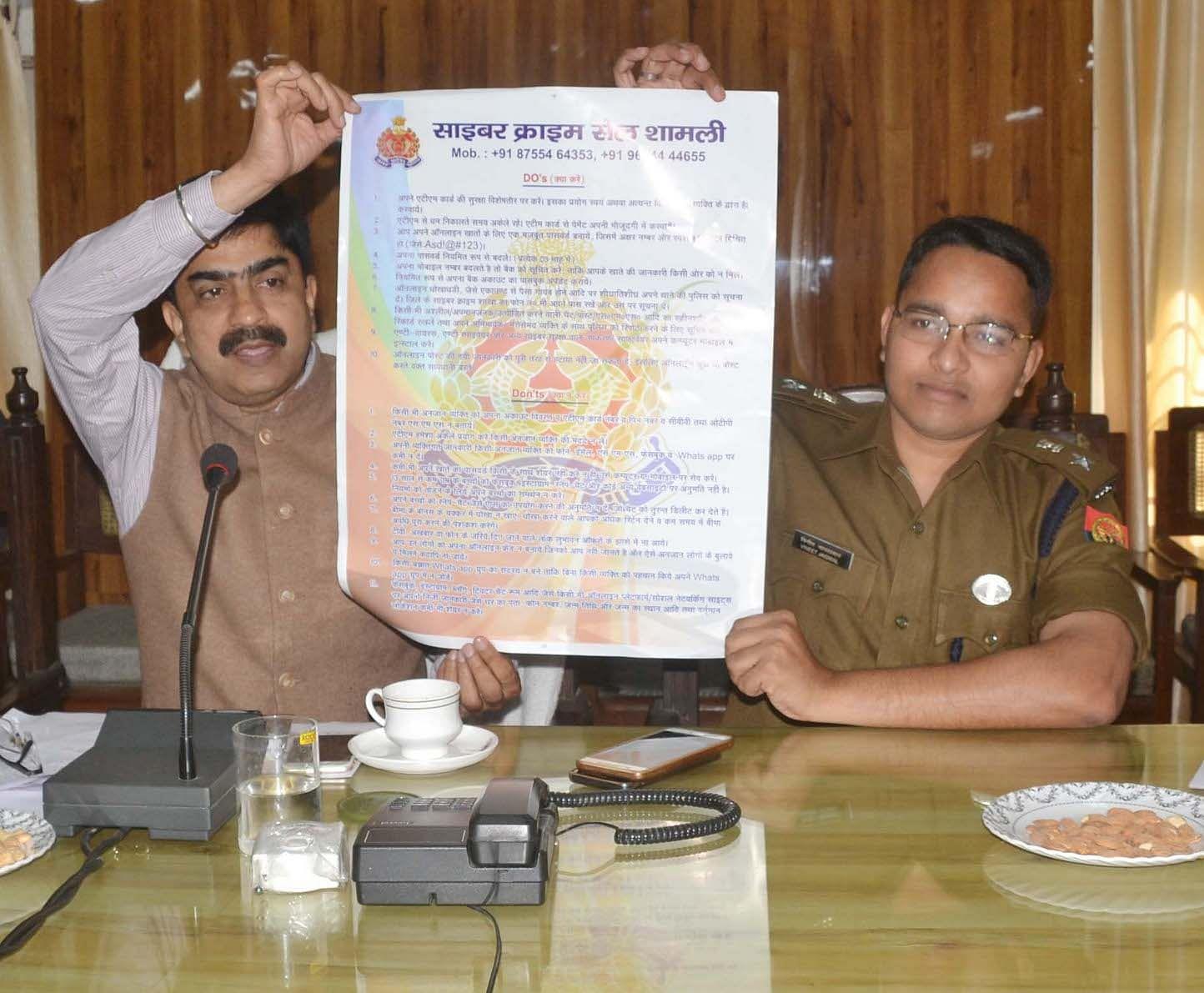 शामली कलेक्ट्रेट में साइबर क्राइम सेल का पोस्टर जारी करते डीएम एसपी