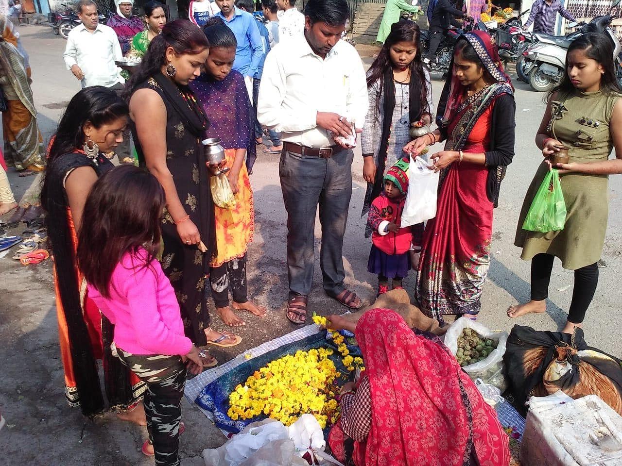 मंदिर के बाहर पूजन सामग्री खरीदती महिलाएं