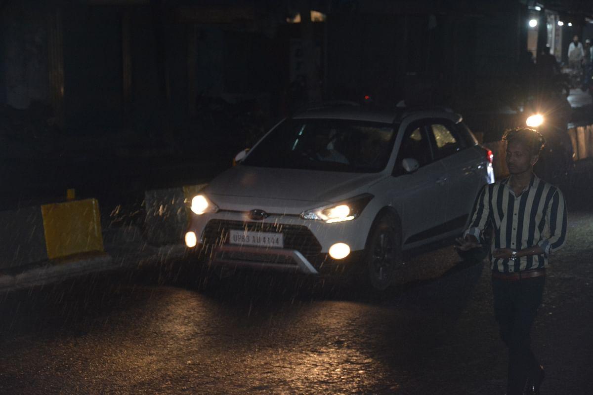 देर रात्रि बारिश में जाते राहगीर एवं वाहन सवार।