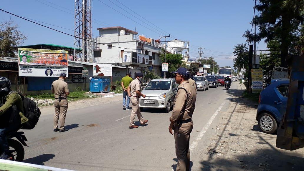 हाईवे पर वाहनों की चेकिंग कर उन्हें निर्देश देते पुलिस कर्मी।