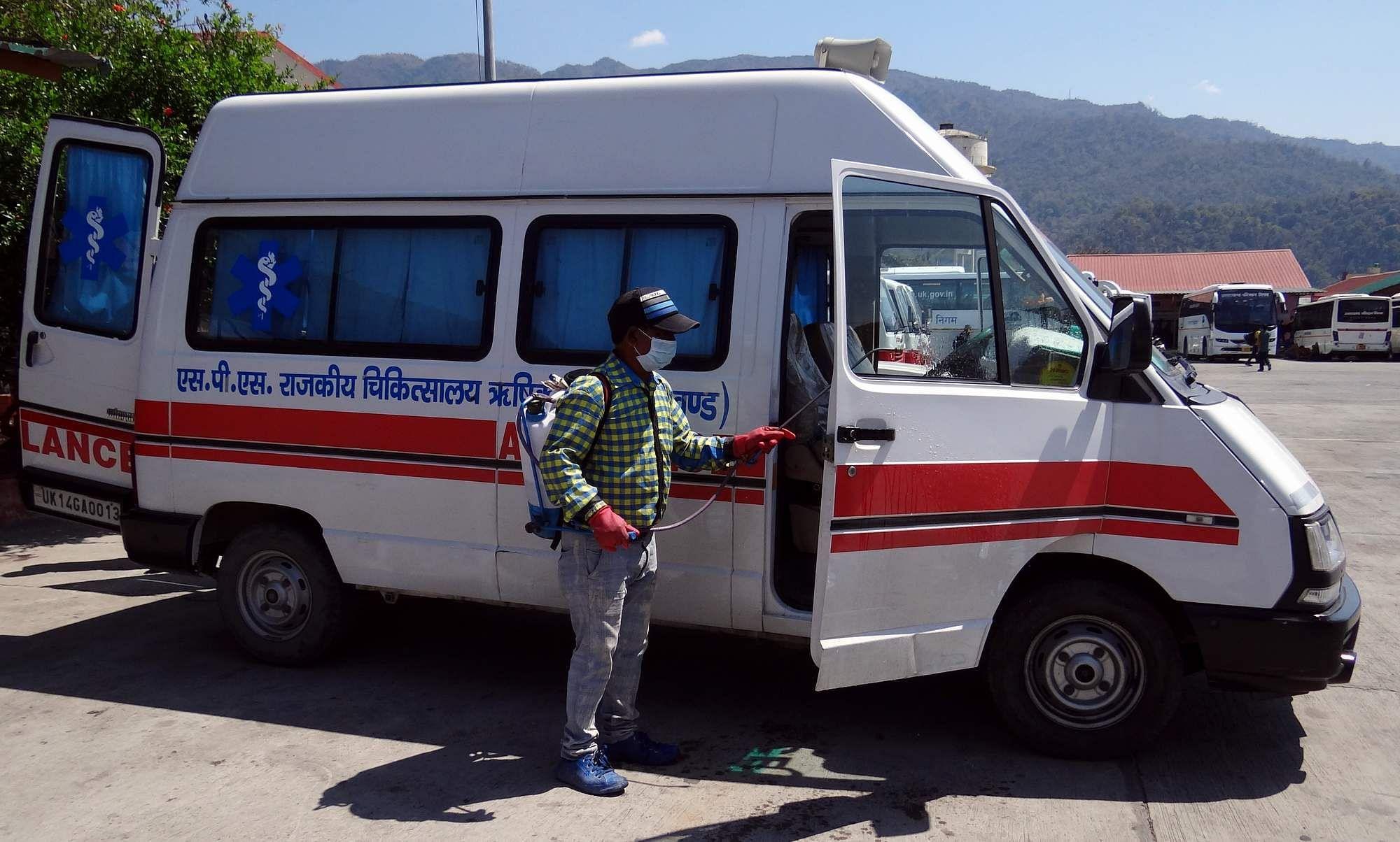 राजकीय चिकित्सालय की एंबुलेंस को सेनेटराइज करता निगमकर्मी।