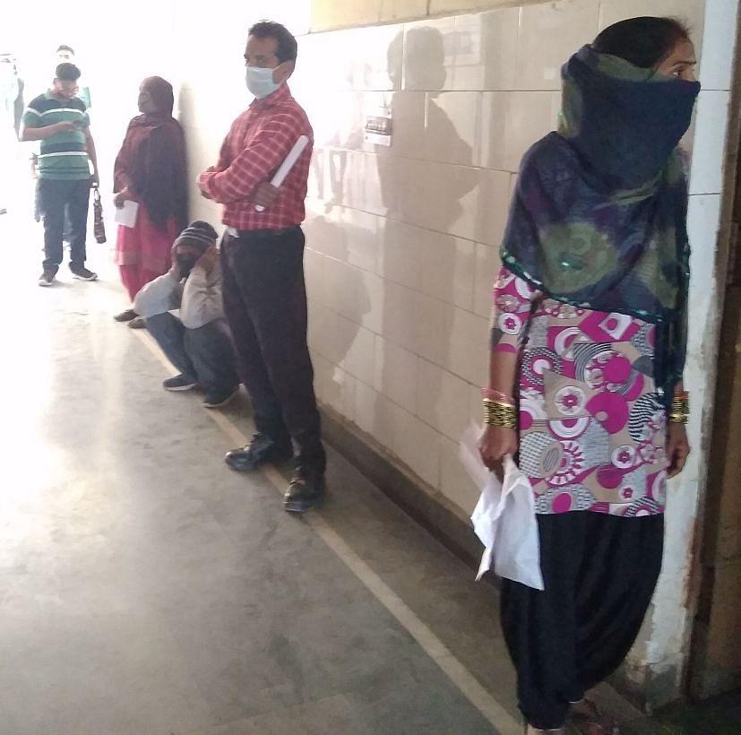 रुद्रपुर जिला अस्पताल की ओपीडी की लाइन में एक-एक मीटर की दूरी पर खड़े मरीज।
