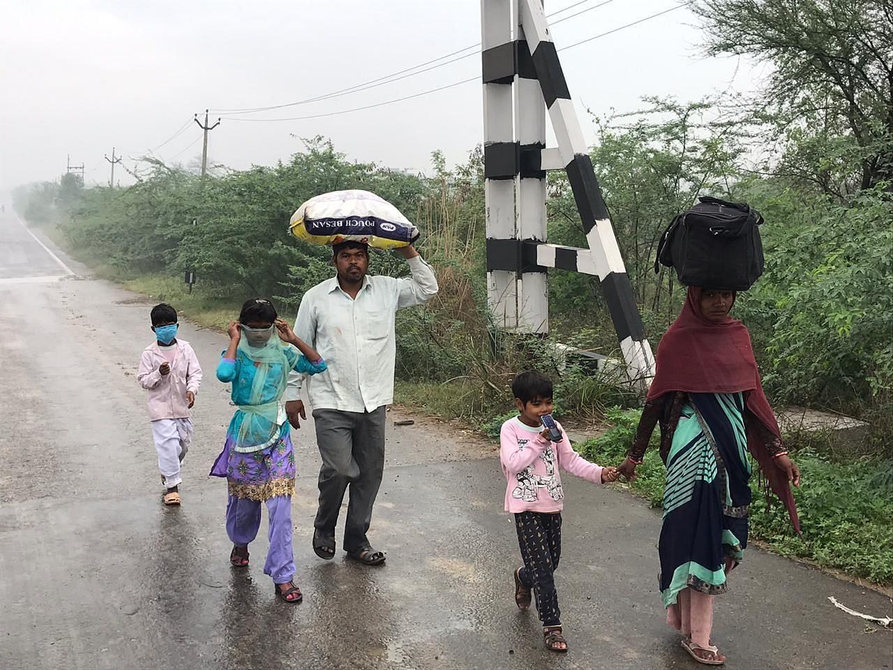 अपने परिवार के साथ यूपी के लिए पैदल जाते लोग।