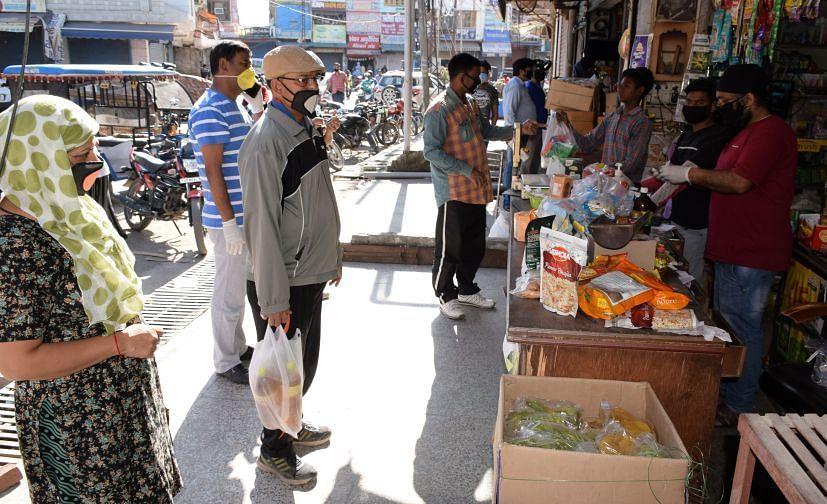 रुद्रपुर के किराना स्टोर में सामाजिक दूरी बनाकर राशन खरीदते लोग।