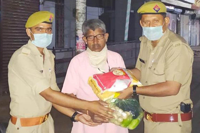 राठ के गुलाबनगर में जरूरतमंदों को राशन देते पुलिसकर्मी