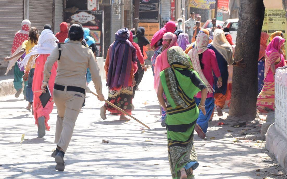 रुद्रपुर में हाईवे पर आई महिलाओं की भीड़ को लाठी भांजकर खदेड़ती महिला पुलिस कर्मी।