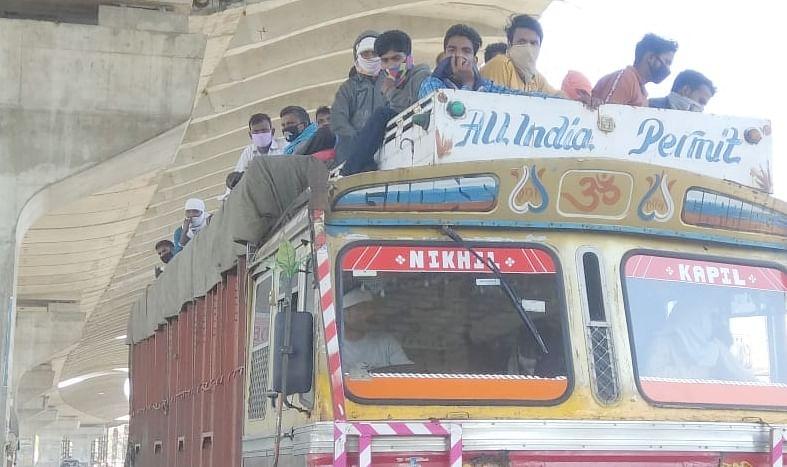 द सरे प्रांतो से लौटते समय ट्रकों के केबिन पर बैठकर जाते मजदूर।