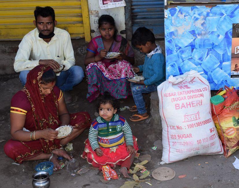 रुद्रपुर के फुलसुंगा में मकान मालिक द्वारा निकाले जाने के बाद सड़क किनारे बैठा परिवार।