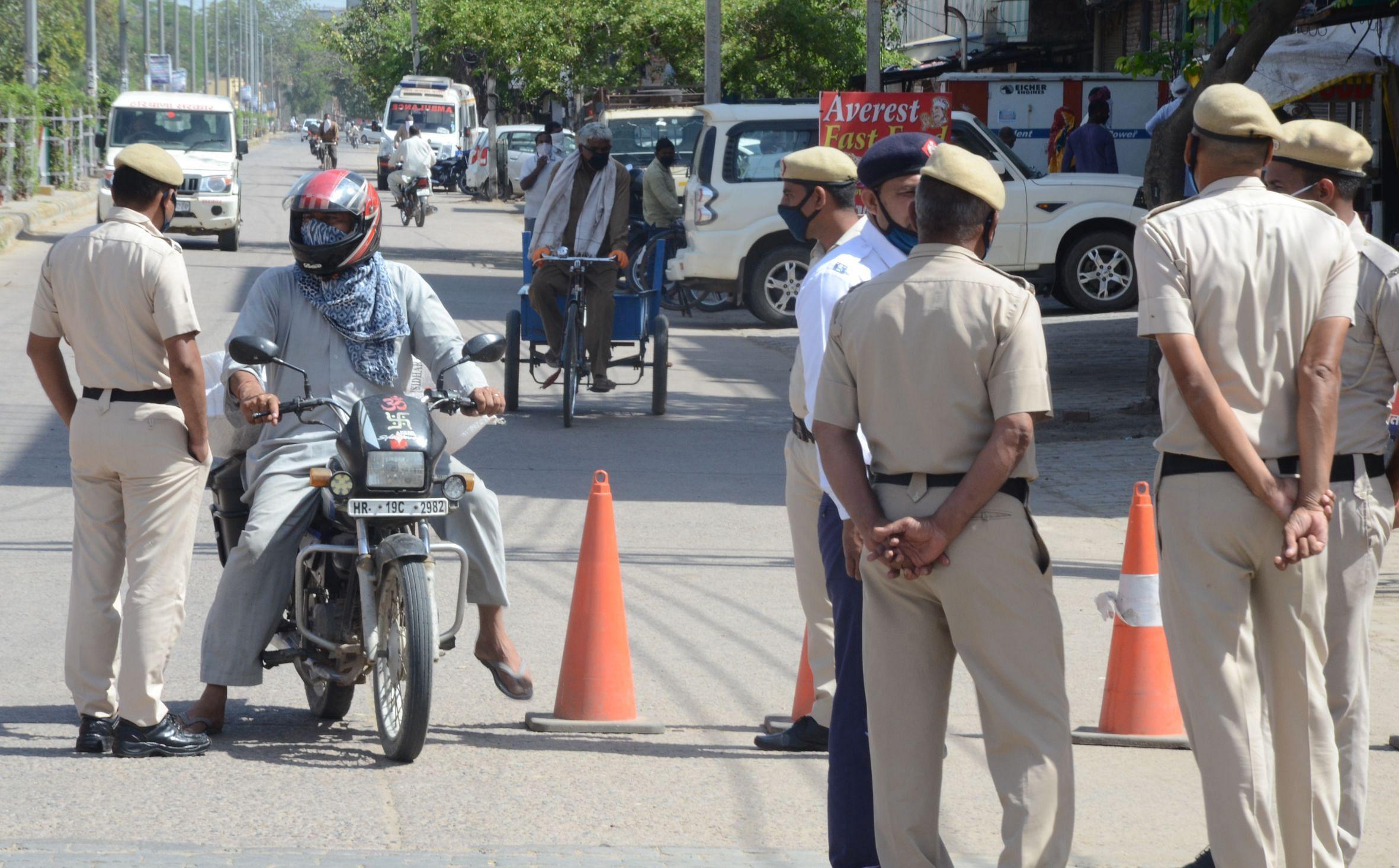 लॉकडाउन में बाहर आने वालों से पूछताछ करते पुलिसकर्मी।