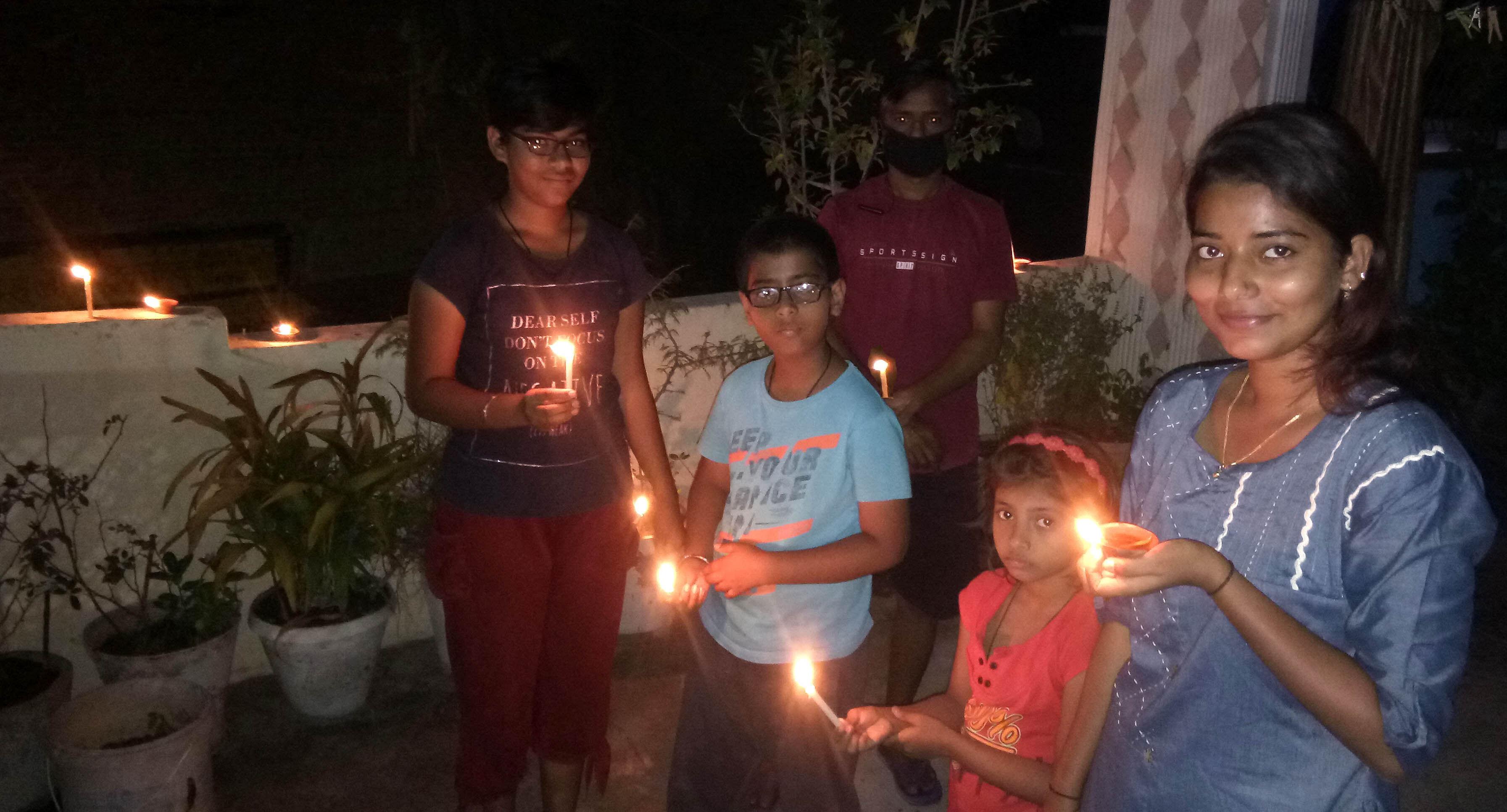 शहर में दीपक और मोमबत्ती जलाकर एकता प्रदर्शित करते लोग।