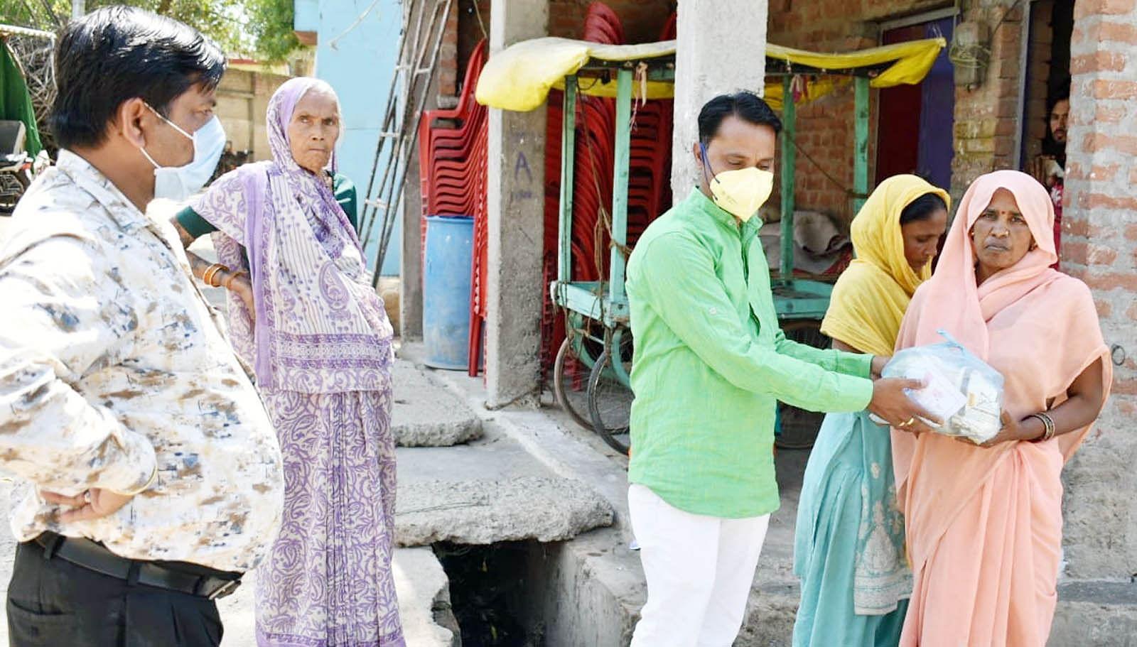 शहर में गरीबों को राशन वितरित करते भाजपा के नगर उपाध्यक्ष अशोक गुरू निषाद।