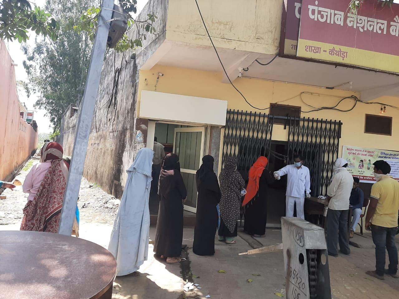 मीरापुर में बैंक के बाहर खाते से रूपये निकालने के लिए लोगों की लंबी लाइन।