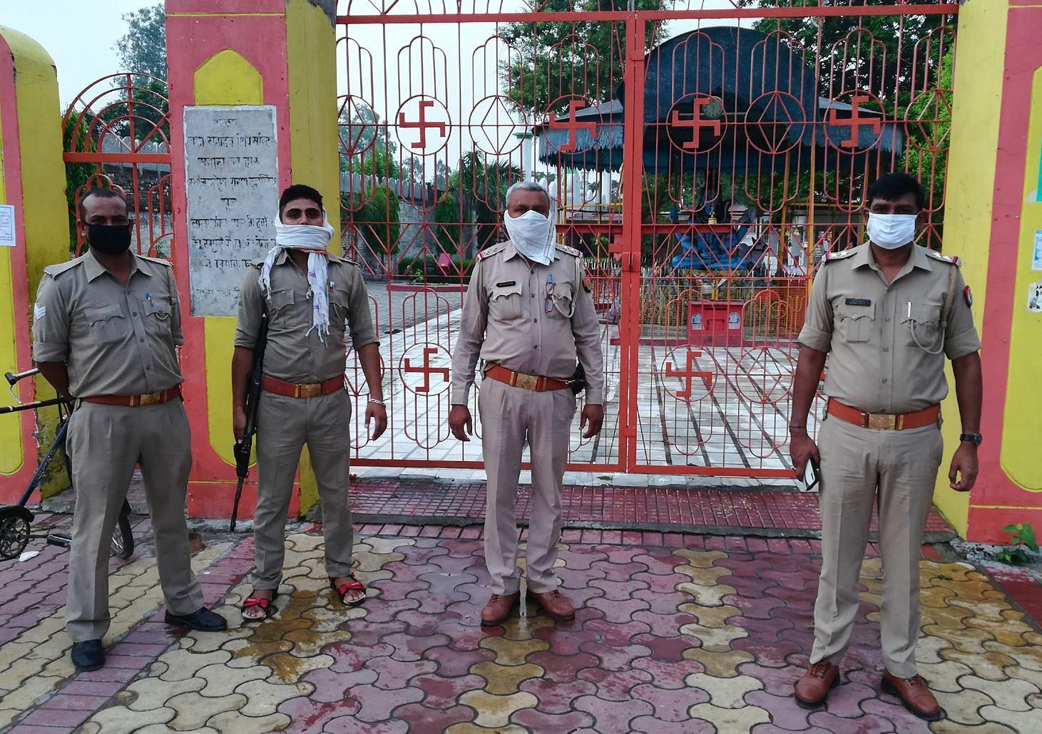 मवाना में बड़े मंदिर का बंद गेट व तैनात पुलिस।