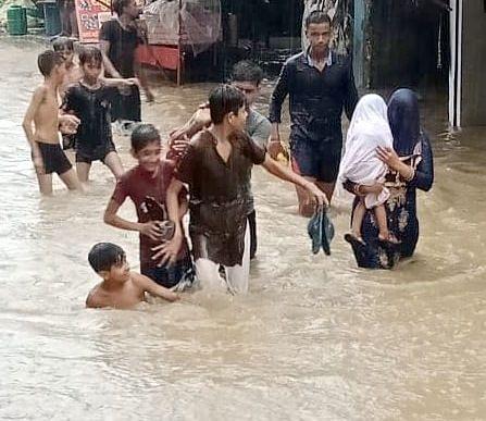 झिंझाना में बरसात के बाद सडक पर  पानी भरने के बाद मस्ती व बच्चे को लेकर गुजरती महिला