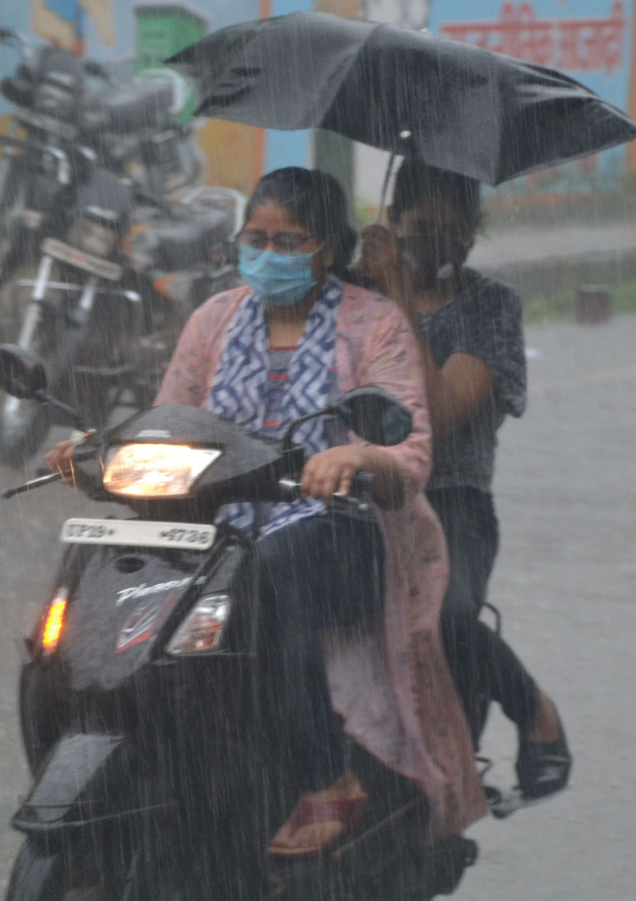 शामली बरसात में स्कूटी पर गुजरती महिला व युवती