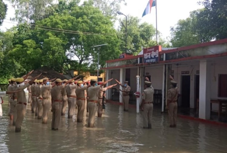 Police men hoists flag amid flood water in Bahraich.