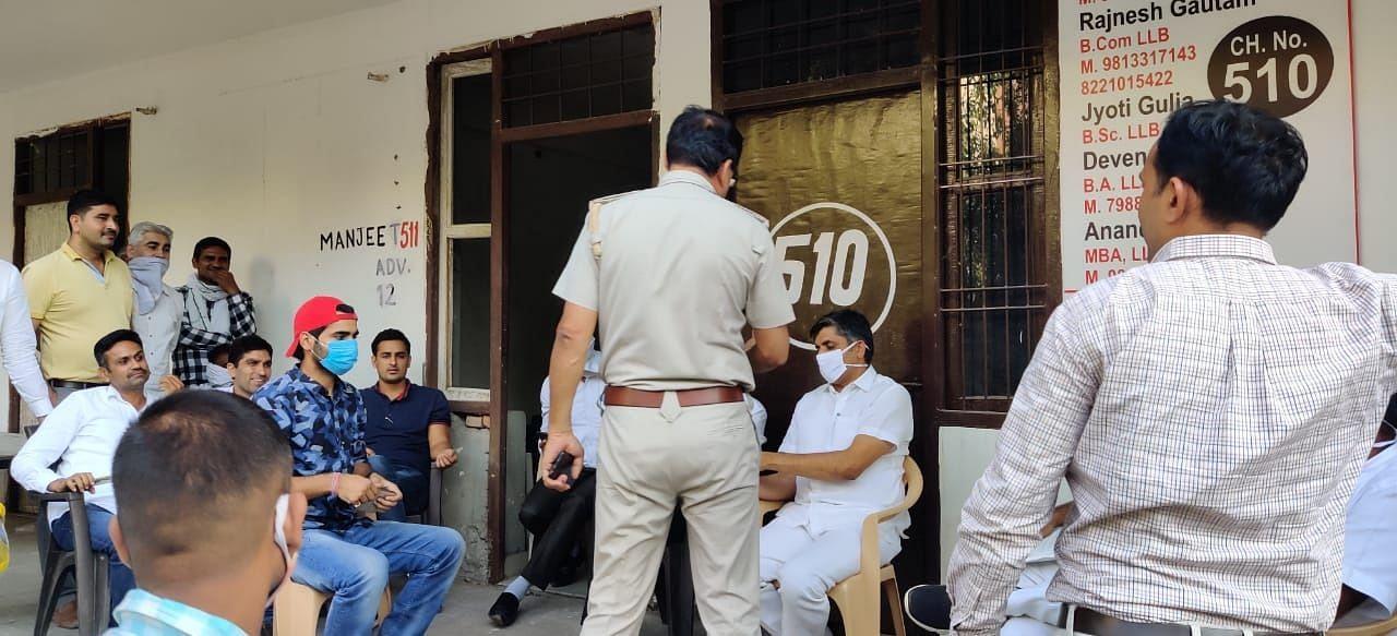 विवाद को निपटाने के लिए वकीलों से बात करते आर्यनगर थाने के सहायक थाना प्रभारी जयभगवान।