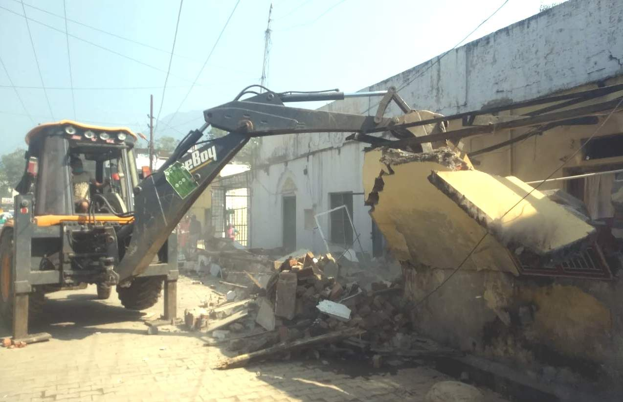 राजकीय प्राथमिक विद्यालय की दीवार को तोड़ती जेसीबी मशीन ।