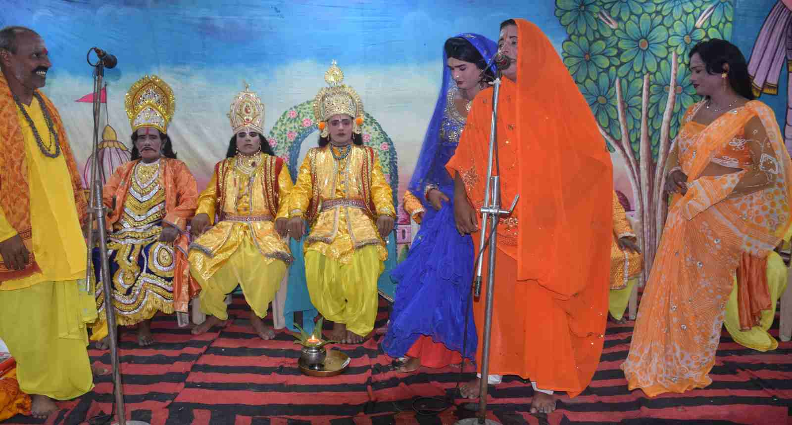 पुरानी कोतवाली में चल रही श्रीरामलीला में मंच पर बैठे बाराती और गीत गाती महिलाएं।