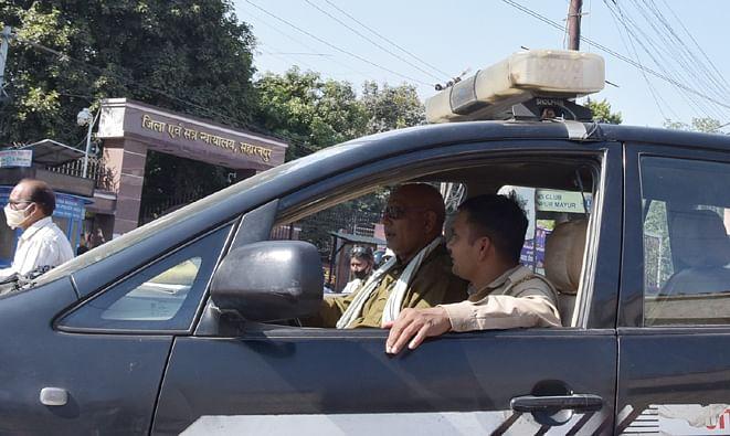 कोर्ट पर बिना मास्क के गाड़ी से जाते पुलिस कर्मी