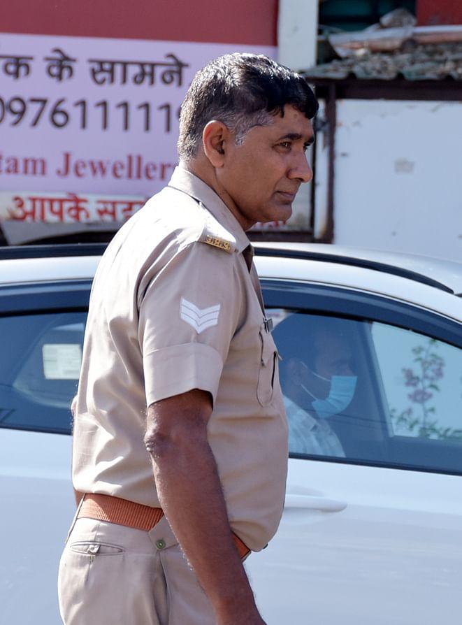 बिना मास्क के दीवानी कचहरी तिराहे गुजरता पुलिस कर्मी