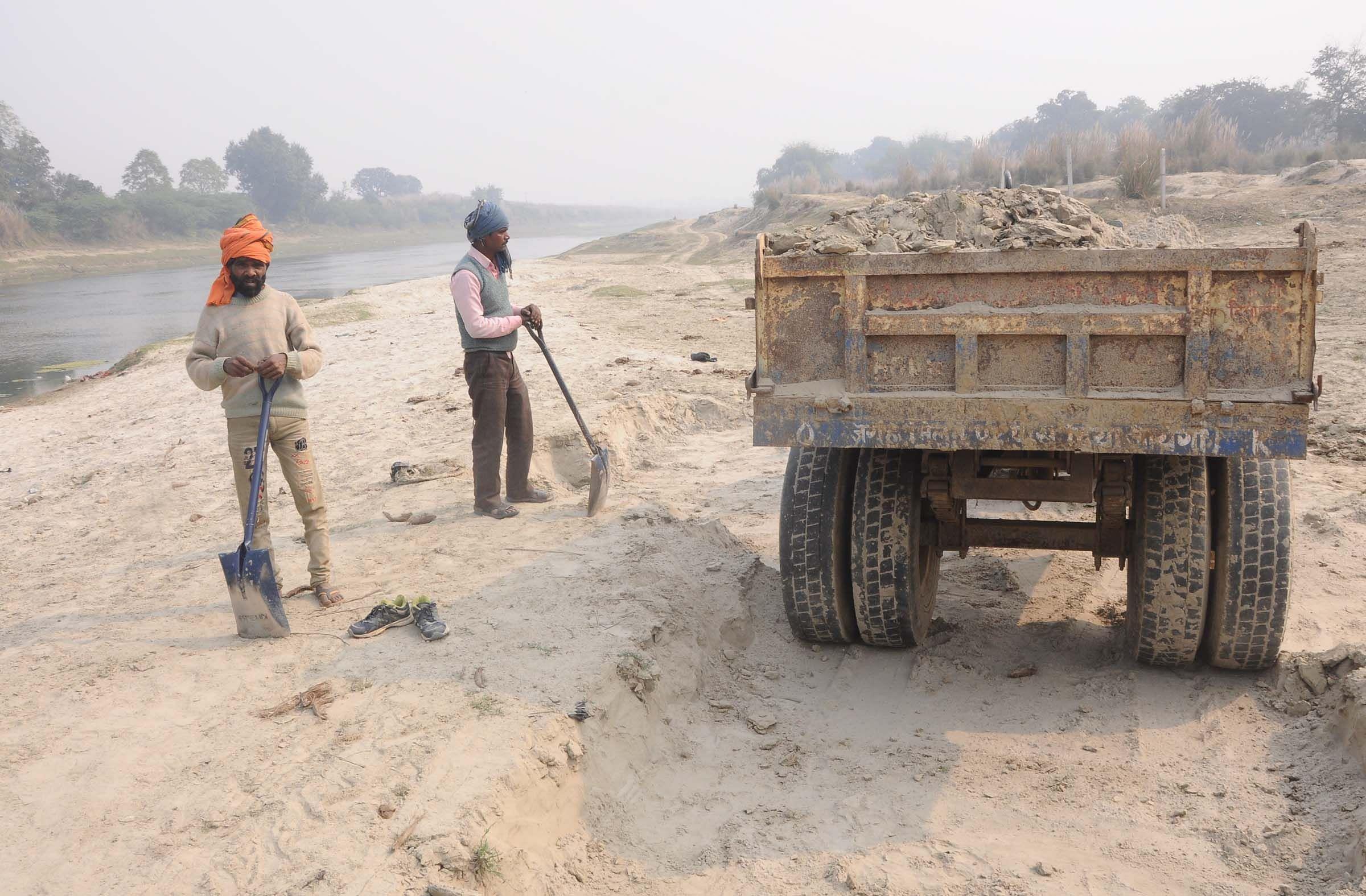 नगर कोतवाली के रेलवे पुल के समीप सई नदी से ट्रैक्टर पर रेत रखते मजदूर।