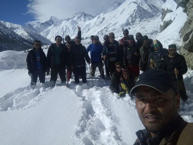 किन्नौर जिले के छितकुल में तीन फीट बर्फबारी होने के बाद गांव के युवकों का एक समूह पैदल चलने के लिए