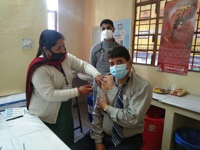 सीएच मार्कंडेय में अधिकारी को कोविड वैक्सीन लगाती स्वास्थ्य कर्मी
