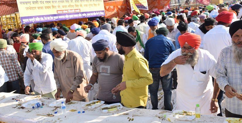 रुद्रपुर में आयोजित किसान महापंचायत में लंगर चखते लोग।