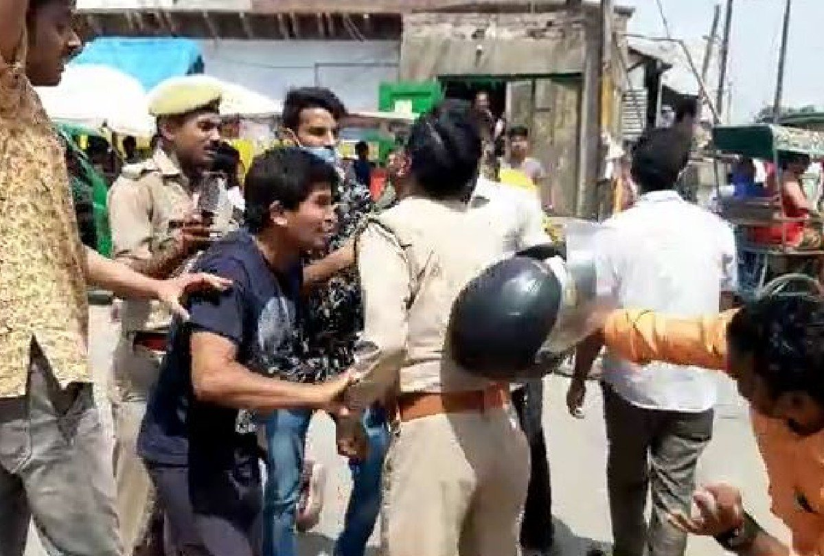 चौराहे पर पुलिसकर्मियों को पीटते युवक
