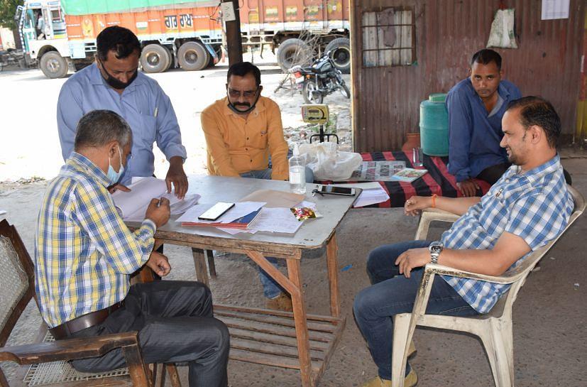 रुद्रपुर गल्ला मंडी स्थित आरएफसी के गेहूं खरीद केंद्र में बैठे कर्मचारी।