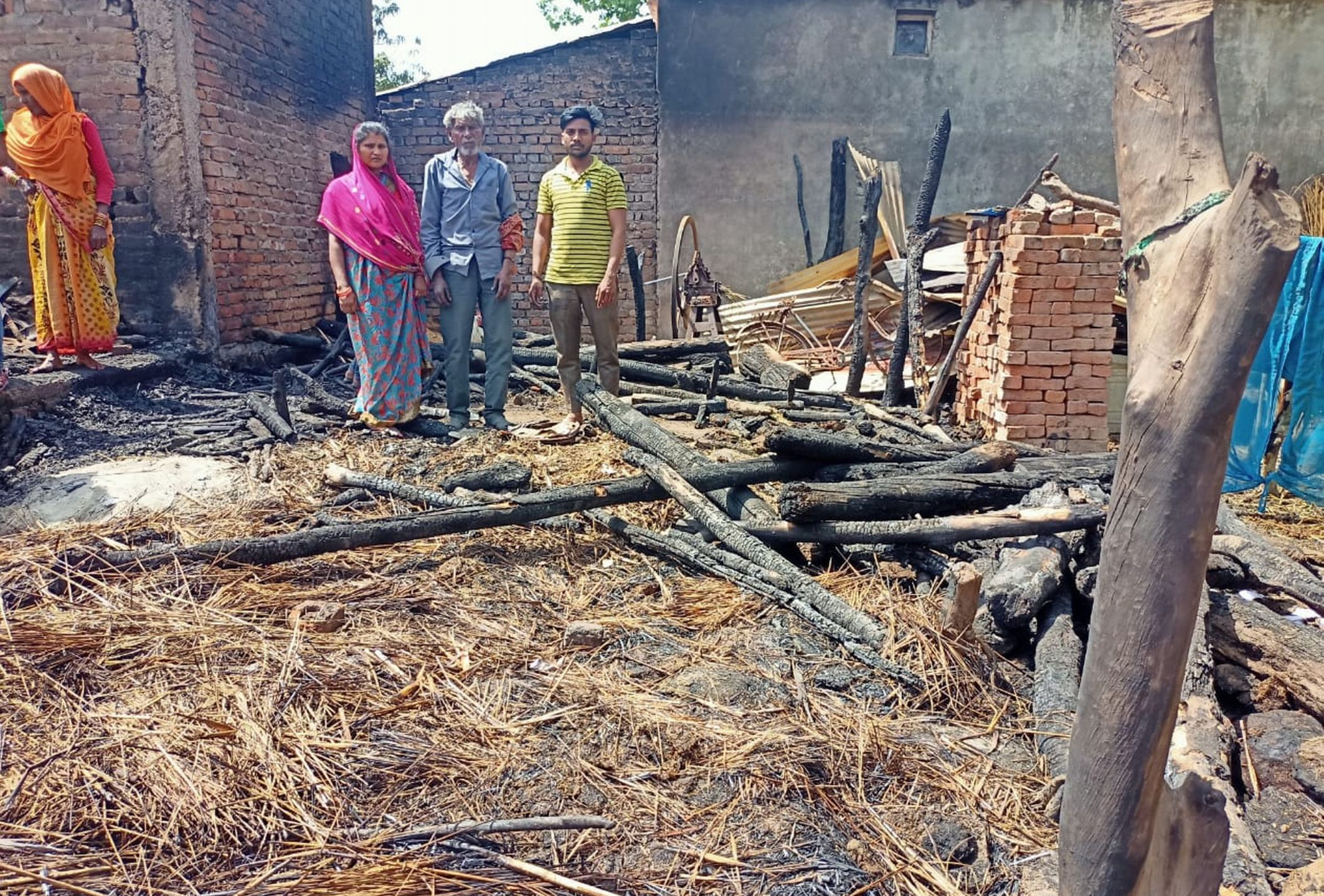 सितारगंज गोठा गांव में आग से राख झोपड़ी दिखाता परिवार।